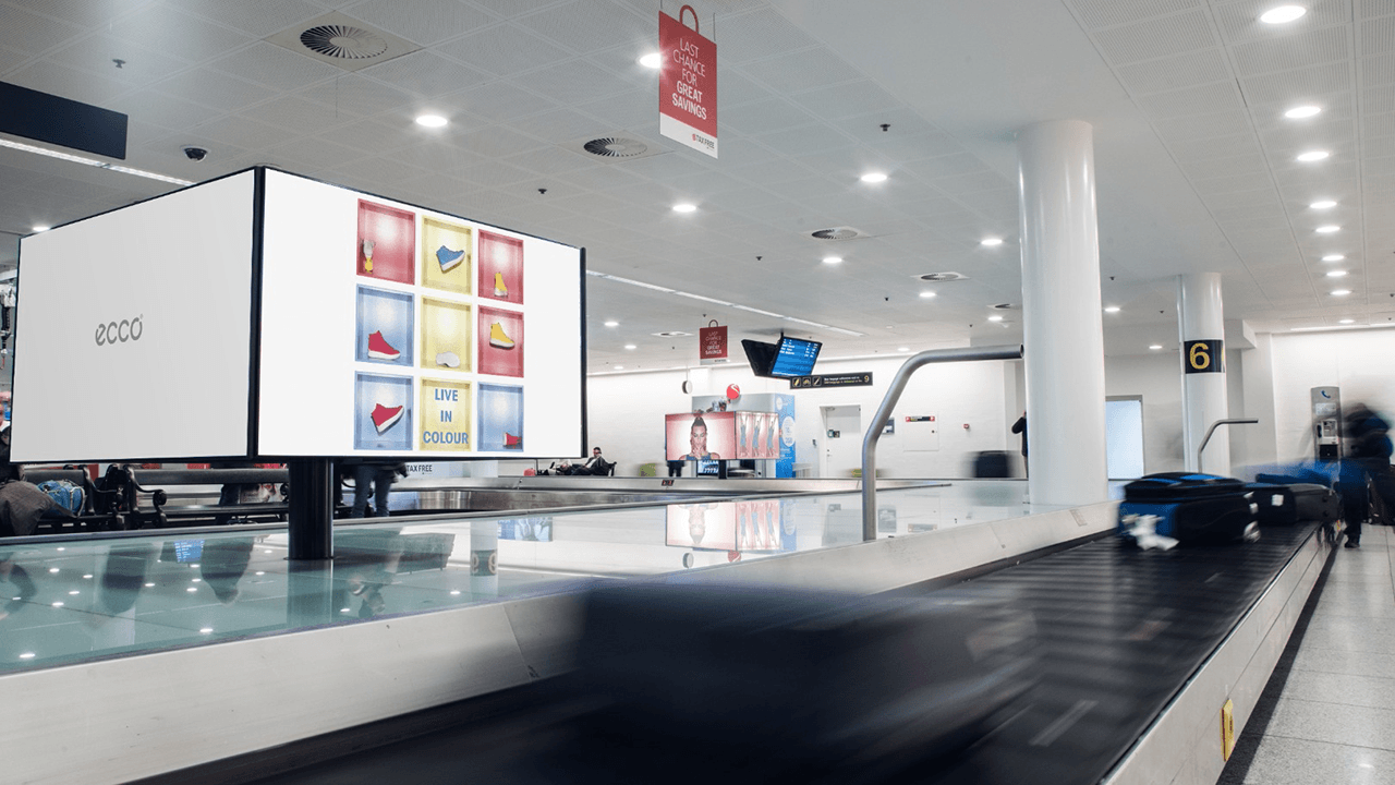 The digital screens by the luggage carousels in Copenhagen Airport's arrival sector are shaped as cubes to create 360° exposure